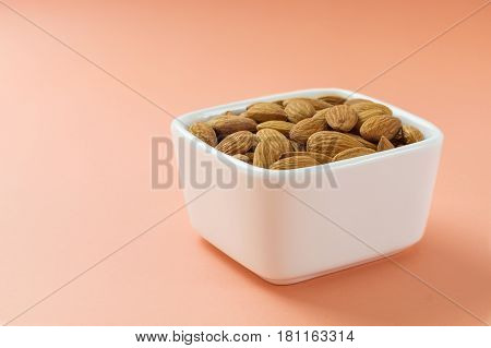 Almonds nuts in white bowl on coral pink background. Source of healthy fat fiber protein magnesium and vitamin E horizontal