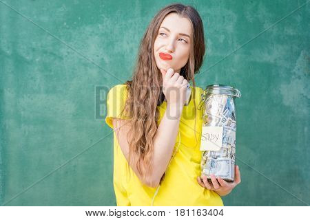 Thoughtful woman in yellow t-shirt holding a bottle with money savings for study