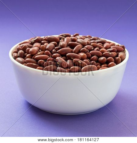 Raw red kidney bean in a bowl on violet background. Vegan source of protein.
