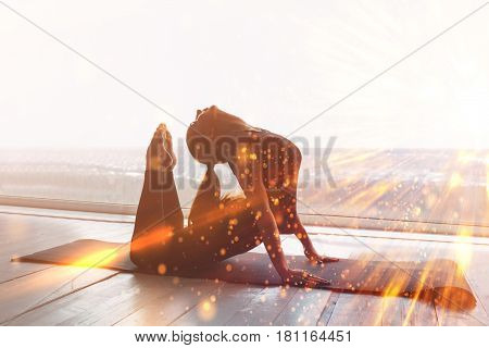 Beautiful woman doing sports (yoga and gymnastics). The concept of practicing sports in the future with visual effects in the form of a flash. Conceptual image of the virtual future of single sports.