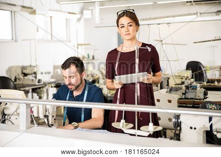 Young Woman Supervising Some Workers