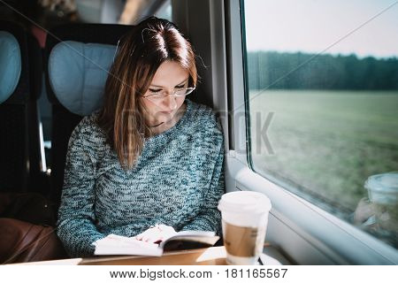 Women reading book on the train siting by the window