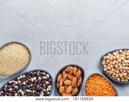 Vegetarian healthy protein sources on gray concrete background. Quinoa, chickpea, almond, red lentils, mixed bean as vegan sources of protein concept. Close up. Top view or flat lay. Copy space.