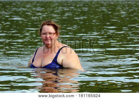 portrait of plump woman bath in river