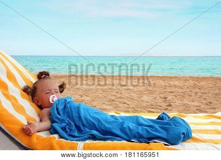 little girl sleeping on beach near sea