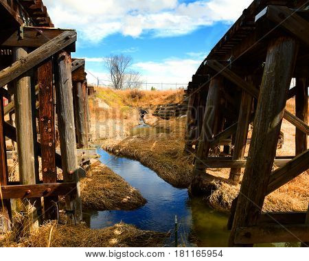 Creek runs between rural wooden railroad tressels in autumn