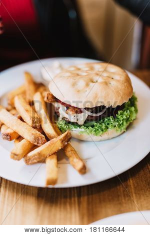 Delicious hamburger with fries on a white plate