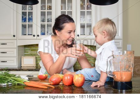 Attractive cheerful woman making smoothie from apples and carrots for small boy, smiling happily