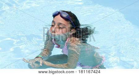 10 year old girl bathes in the swimming pool with her diving glasses