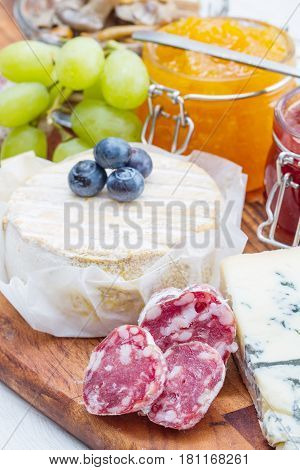 wooden cutting board with cheese cold cuts and jams