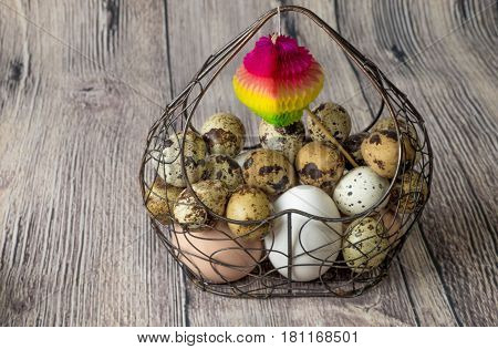 a lot of chicken eggs and quail eggs beige and white lies of a metal structure in the shape of a heart lying on a wooden table