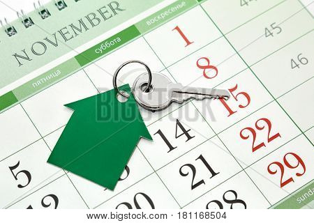 The key and the house of paper on the background of the calendar