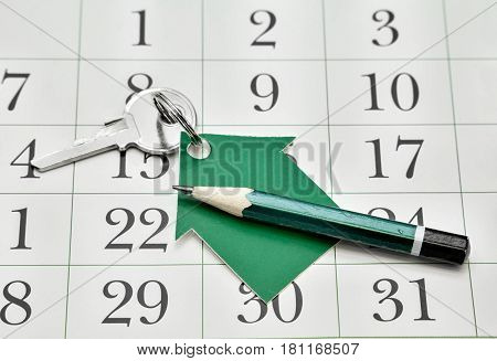 Key a house made of paper and a pencil against the backdrop of a calendar. Business Details