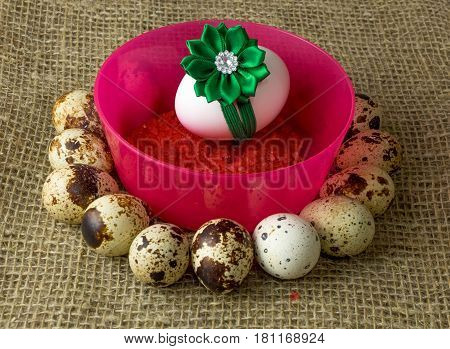 quail eggs and chicken egg with green bow are in a circle around the plastic pink bowl of red salt on a wooden table with natural burlap