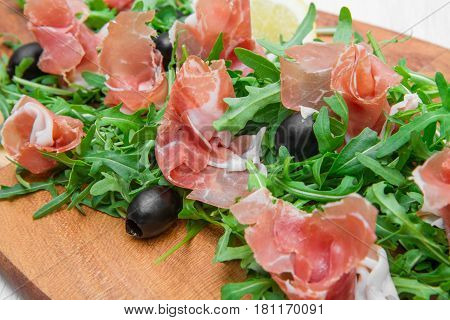 Chopping Board With Aragula And Raw Ham