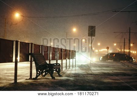 Snowstorm blowing around the bench at night.
