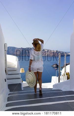 Elegant lady on holidays in Santorini Greece enjoying the view