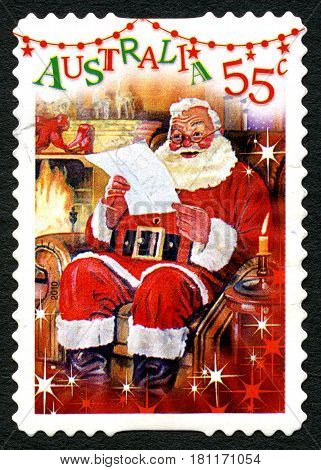 AUSTRALIA - CIRCA 2010: A used postage stamp from Australia depicting a festive scene of Santa Claus reading a letter by the fireplace circa 2010.