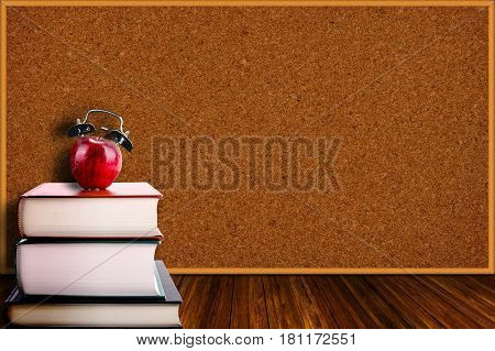 Apple Alarm Clock On Stack Of Books And Corkboard Background
