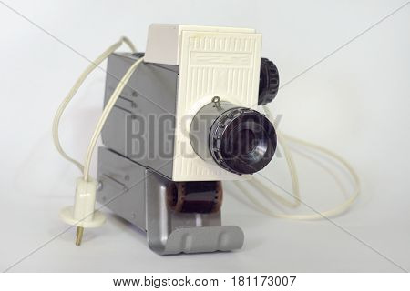 Vintage slide projector loaded with film. Front view on lens