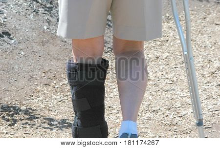 Female with a sprained leg trying to walk with a crutch.