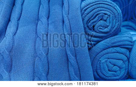 Blue knitted fabric twisted into a roll.