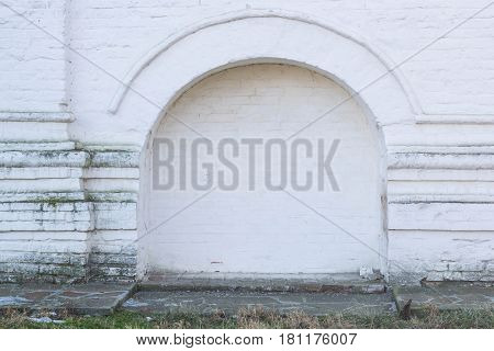 The walled-up door with stone arch in an ancient white plastered wall background photo frame place for text