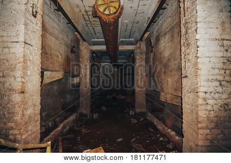 Basement in old abandoned industrial production building or factory, brick walls, pipes, perspective
