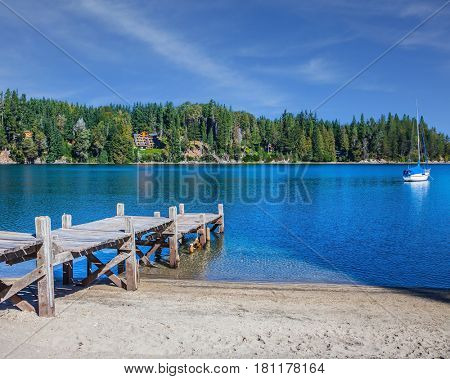 Wooden boat pier on the lake.  The water of shallow lake reflects forest. Bariloche, Argentina. The concept of exotic tourism