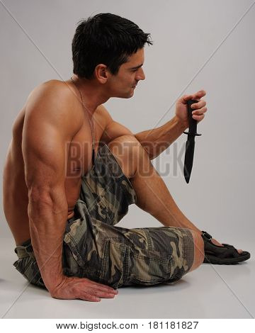 The defiant military man is holding a knife.