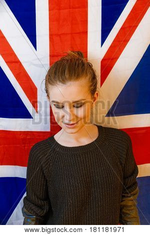 Androgyne girl looking dawn in front of Union Jack Flag Vintage Color.
