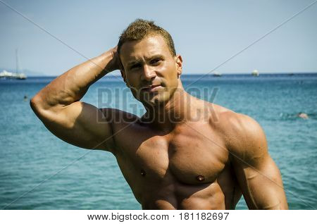 Handsome young bodybuilder getting out of sea or ocean water looking at his muscular torso, pecs, arms and abs