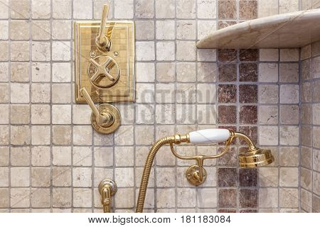 Vintage faucet and shower. Gold color in the bath.