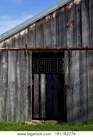 Rural old barn door opening with gate, blue skies and green grass