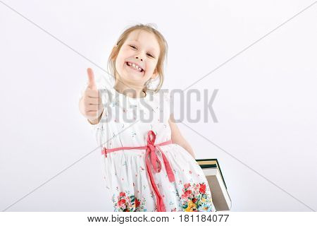 A little cheerful girl with textbooks. Studio shot