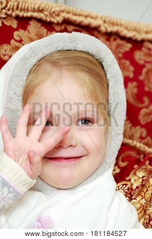 A cute little girl in a white hood looks through her fingers.