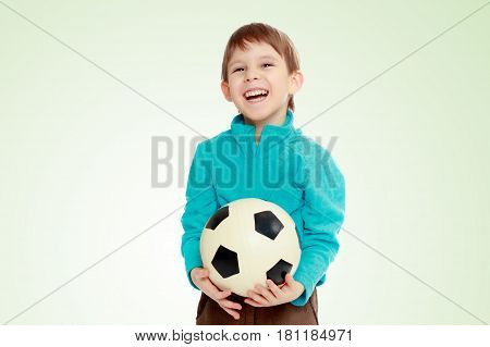 Little boy in brown pants and blue shirt playing with a soccer ball.From fun boy laughs out loud.
