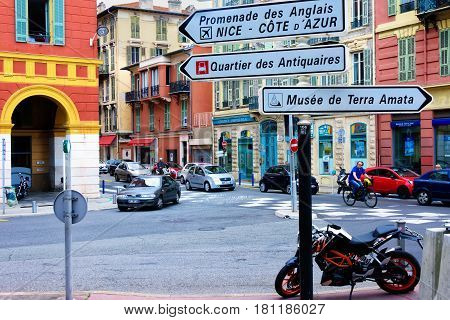 Nice France - June 8 2016: A central busy street in Nice France filled with retail stores pedestrians and automobiles