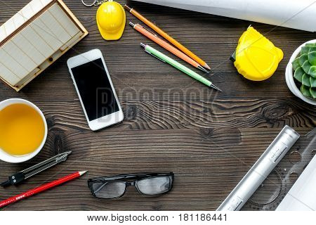 Construction office with architect working tools and cup of tea and mobile on wooden table background top view