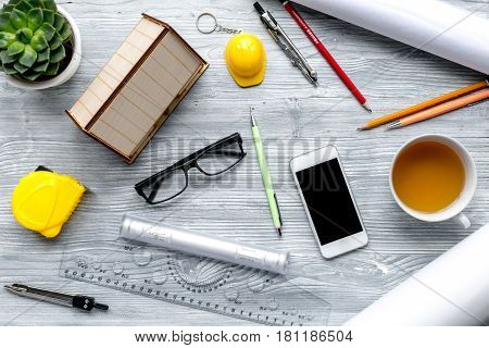 profession concept with architect desk and constructor tools and phone on light wooden background top view