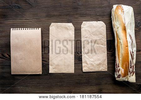 food delivery service workdesk with paper bags and sandwich on wooden background top view space for text