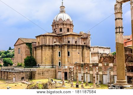 The ancient ruins of the once Roman Forum surrounded by other ancient govermental buildings.