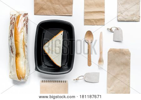 delivery service set with paper bags and sandwich on white desk background top view space for text