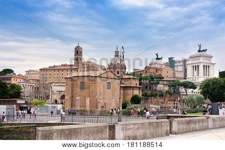 Rome Italy - June 10 2016: Pedestrians observing the ancient ruins of the once Roman Forum surrounded by other ancient govermental buildings and structures.