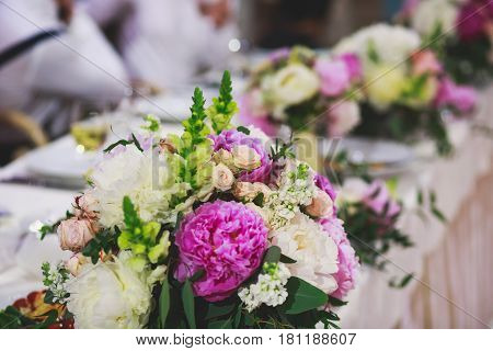 Beautiful wedding interior and table decor, flower decoration with flowers bouquet, with roses, tulips, peonies, elements of outdoor wedding ceremony