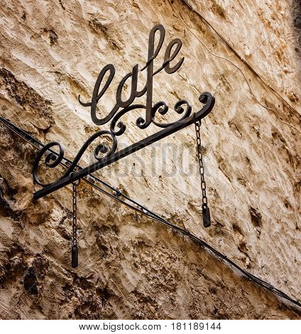 Old iron Cafe sign with metal scroll attached to wall