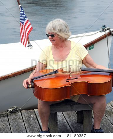 Mature female senior with her cello on the lake outdoors.