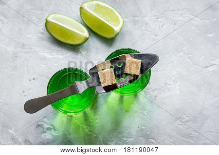 green absinthe with sugar cubes in spoon on stone table background top view