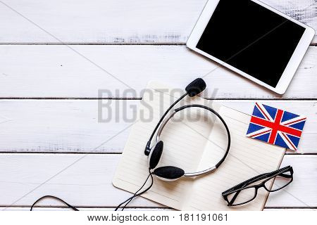lifestyle learning english online with flags and tablet on white wooden table background top view mockup
