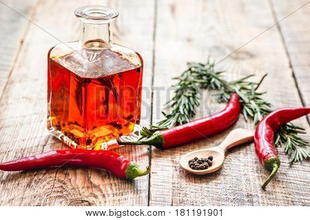 Glass bottle with chili oil and herbs on wooden table background